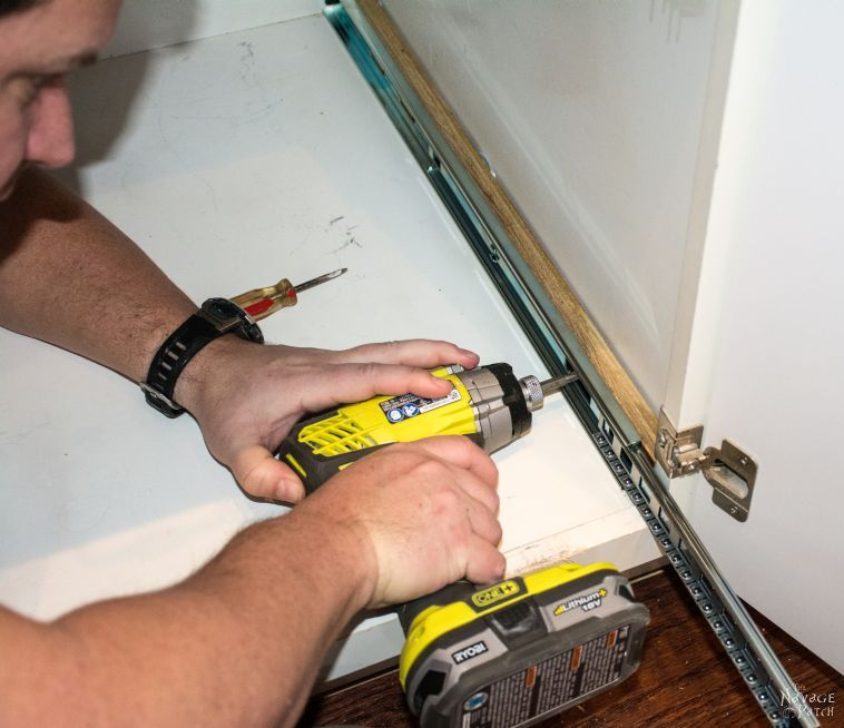 man installing drawer slides in a cabinet