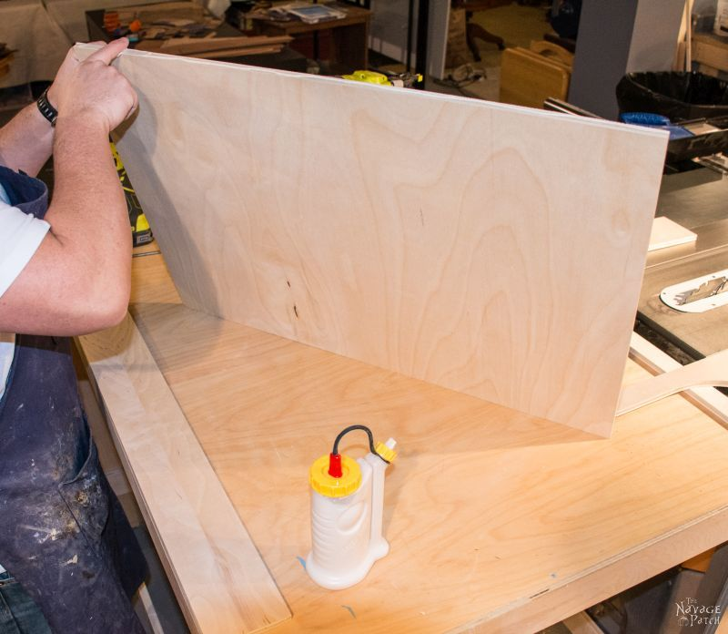 man putting glue on a piece of plywood to build sliding shelves