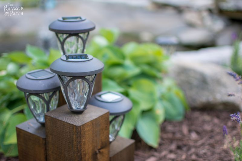 group of cedar post solar landscape lights in a garden