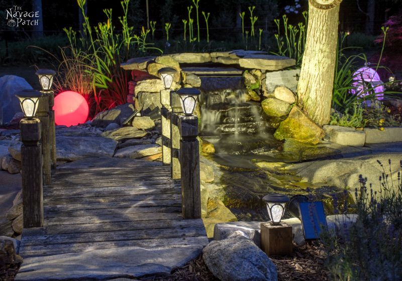 cedar cube solar landscape lights in a garden at night
