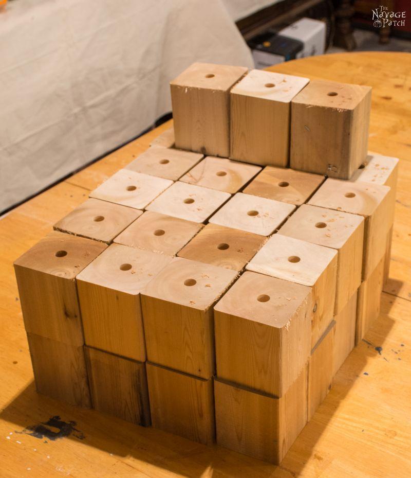 stack of cedar cubes with holes drilled their tops
