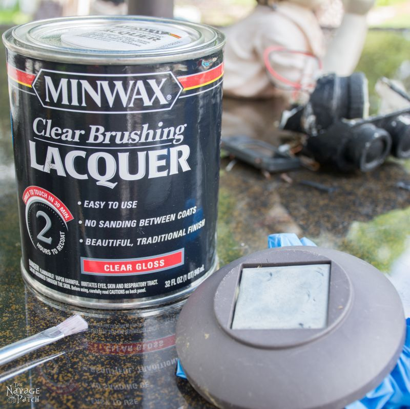 can of lacquer next to a landscape light with a hazy solar panel