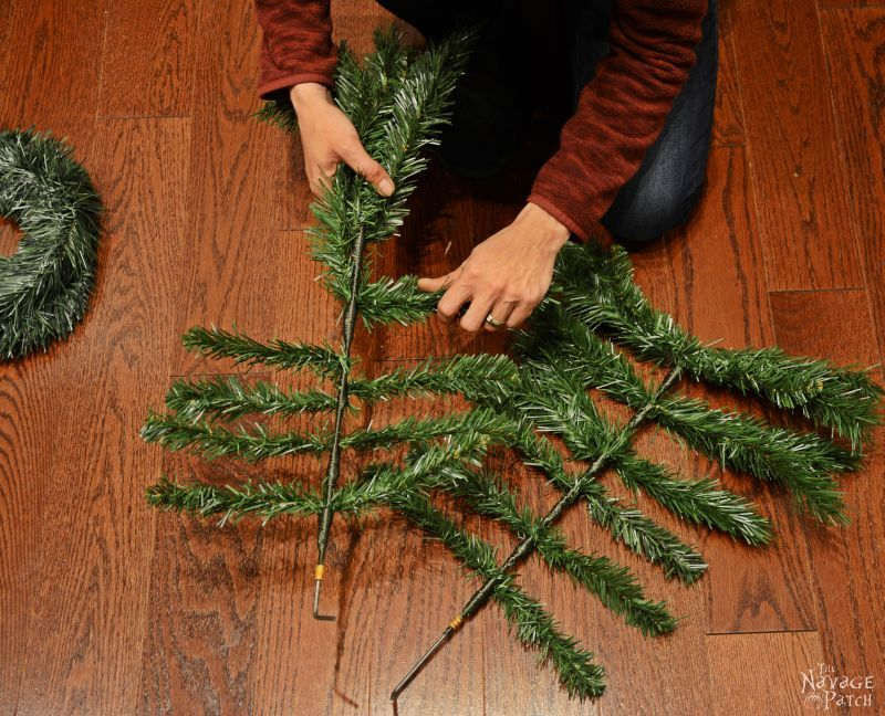 woman bending faux christmas tree branches