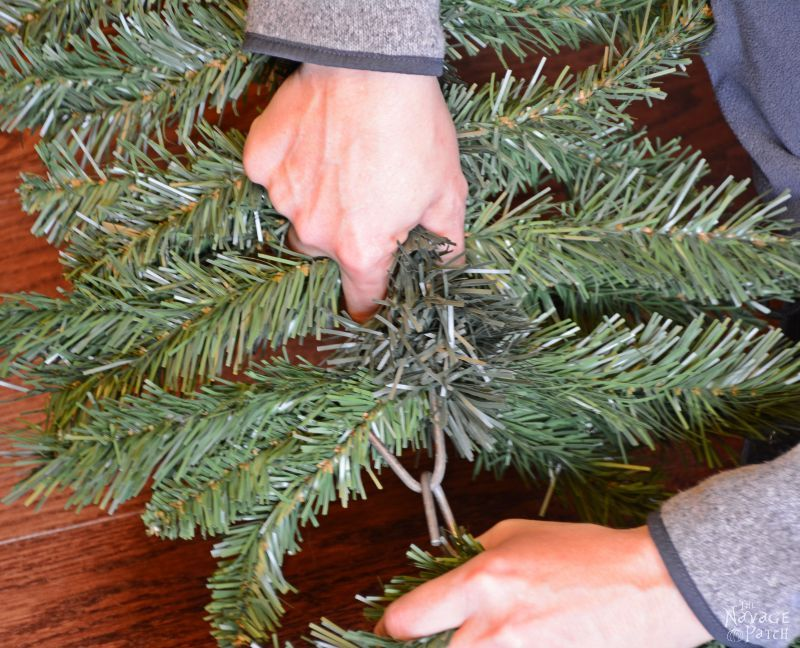 woman connecting two fake christmas tree branches together