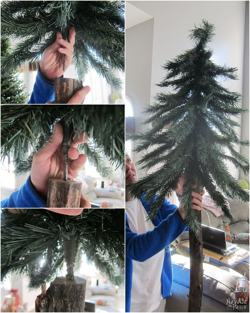 woman hanging faux christmas tree branches from a real tree branch