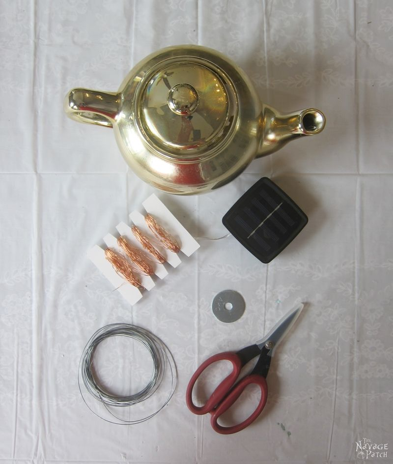 teapot, solar string lights, wire and scissors on a table