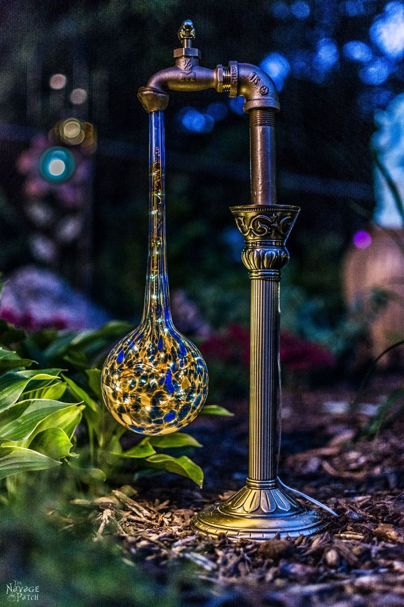 side view of a waterdrop solar light in a garden at dusk