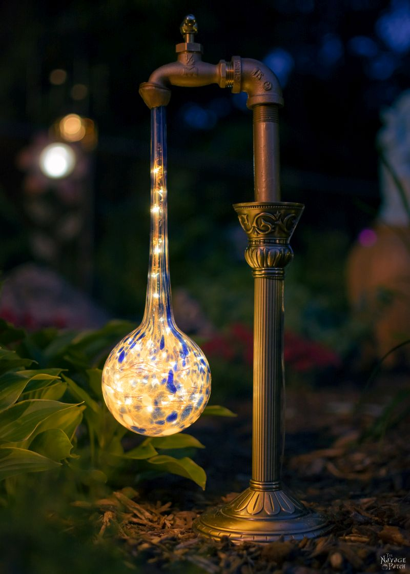 closeup of waterdrop solar light next to a plant at night