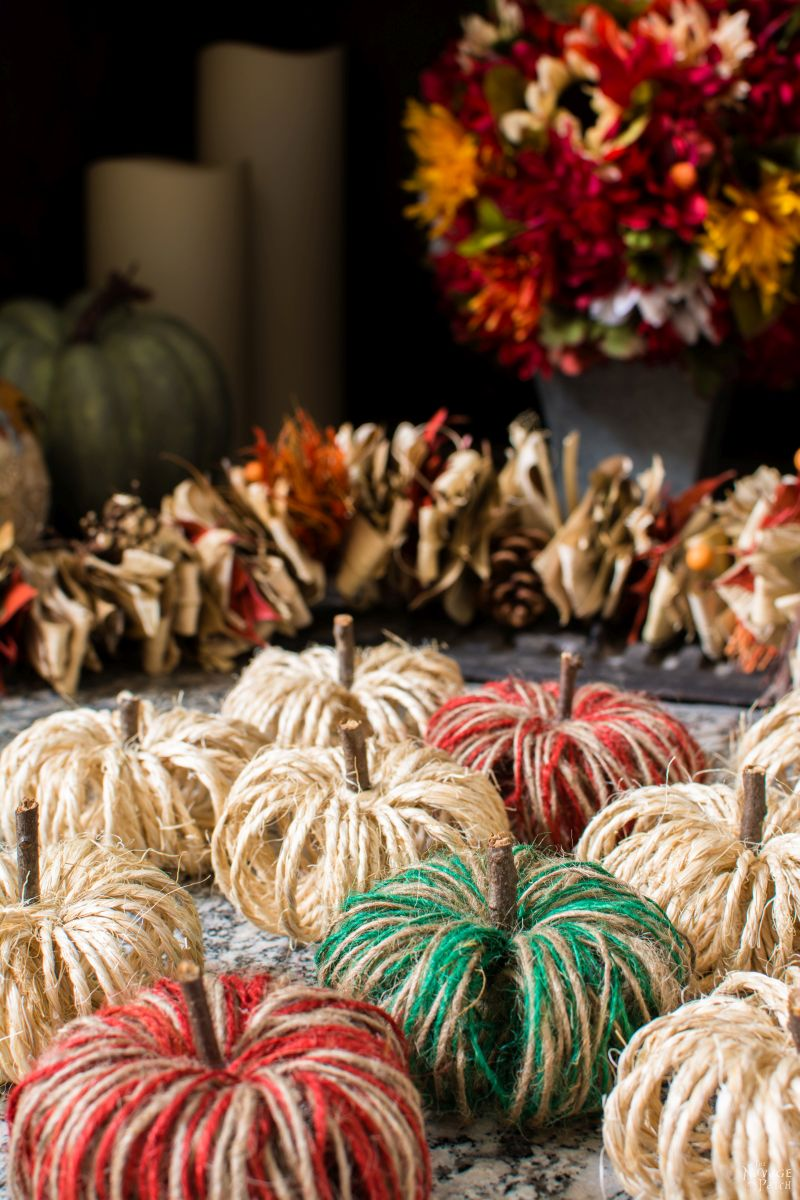 a group of diy sisal twine pumpkins on a hearth