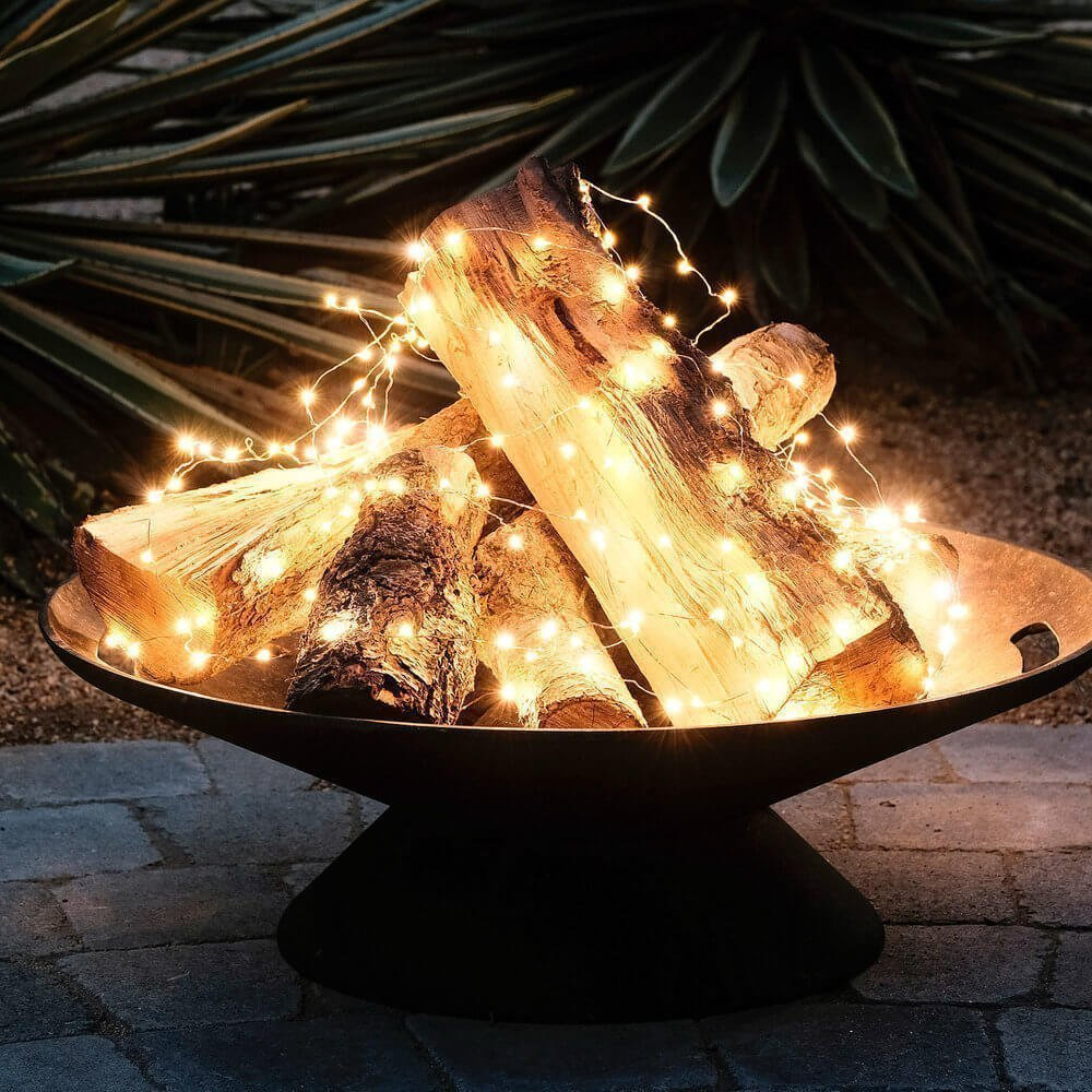 logs in a firepit with starry string lights