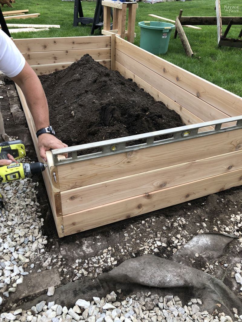 man drilling a raised bed