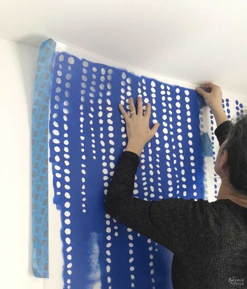woman placing a wall stencil on a white wall