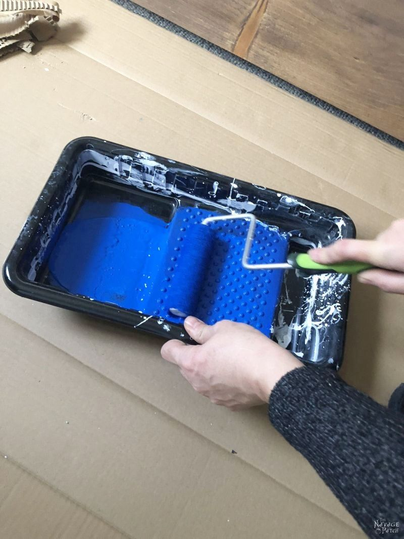 woman loading a paint roller with blue paint