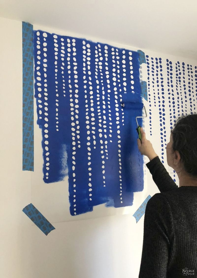 woman stenciling the wall with blue paint
