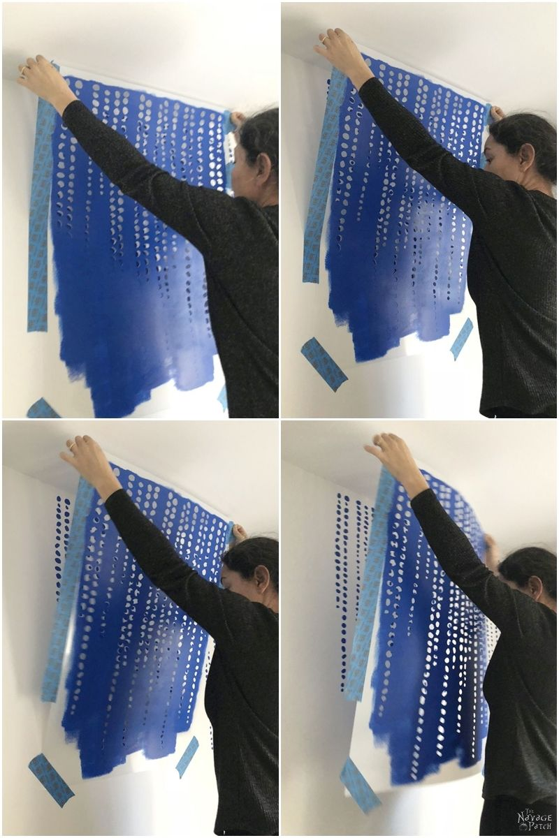 woman peeling the stencil off of the wall