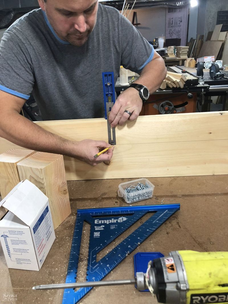 man tracing a line onto a board