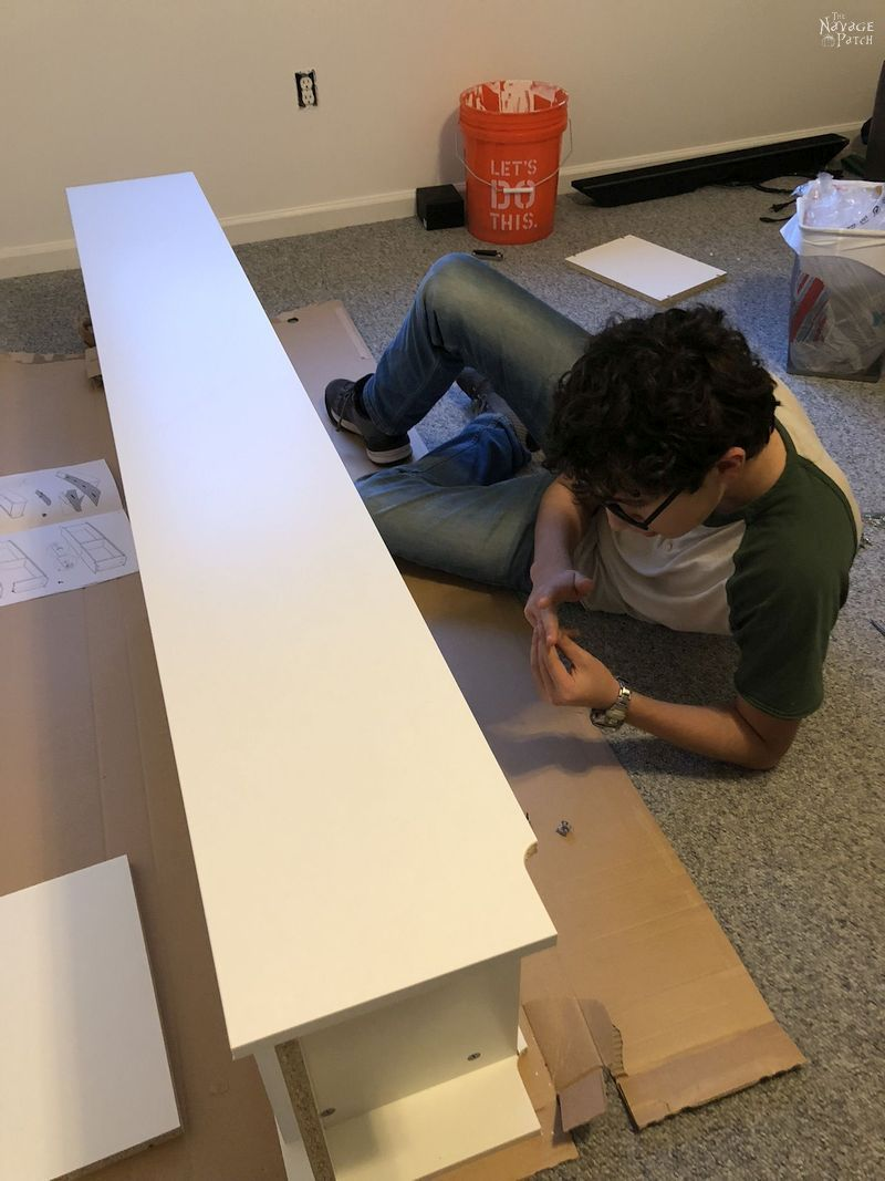 boy examines injured finger while building IKEA furniture on the floor