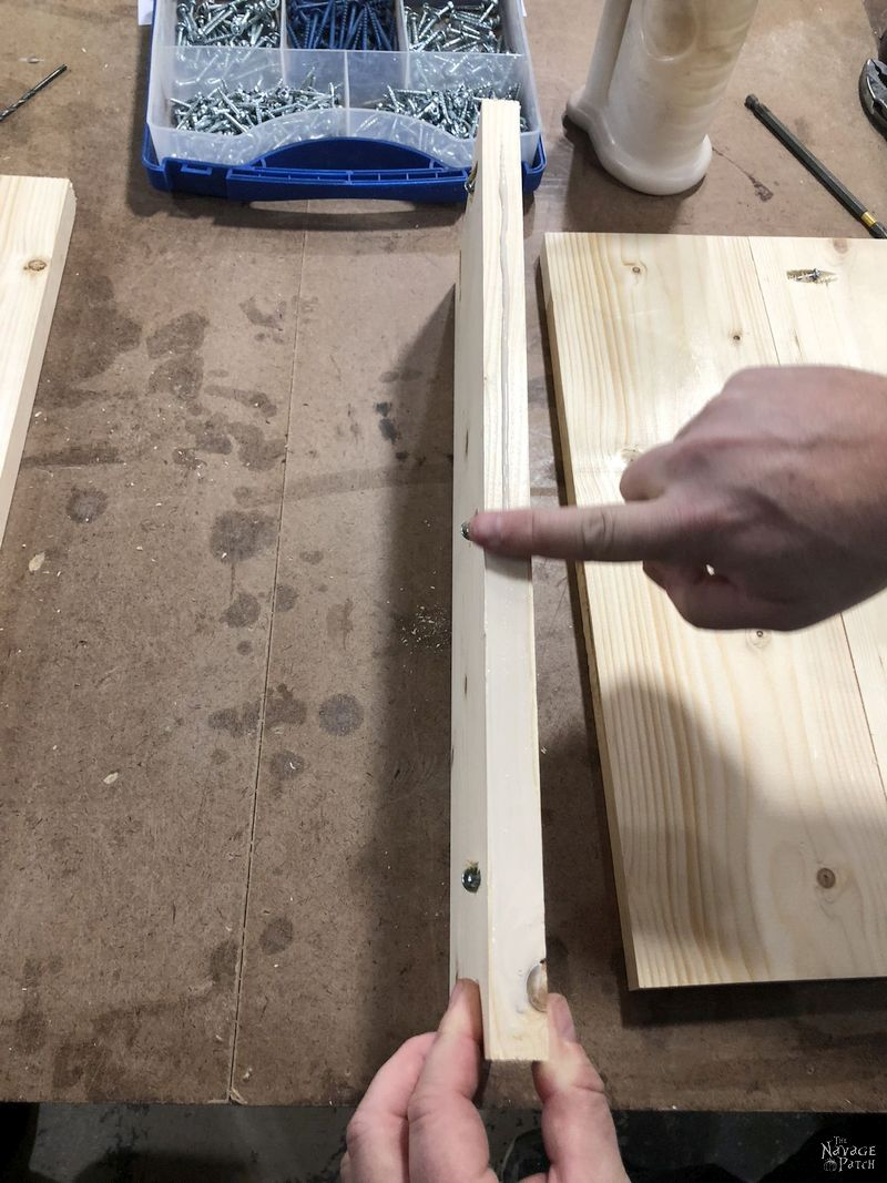 finger applying a bead of glue to the edge of a board