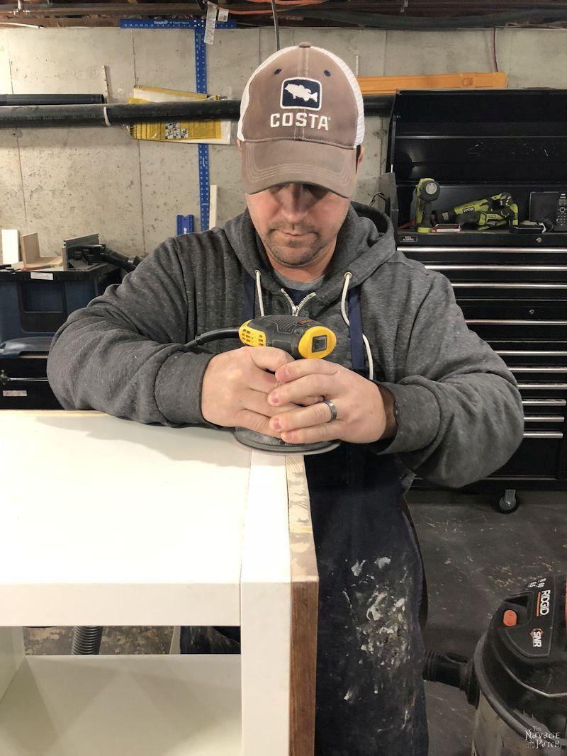 man wearing baseball cap sanding an ikea kallax