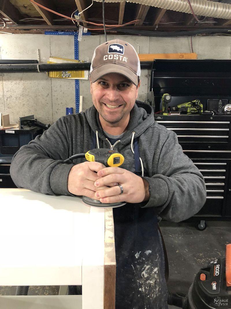 man smiling while sanding