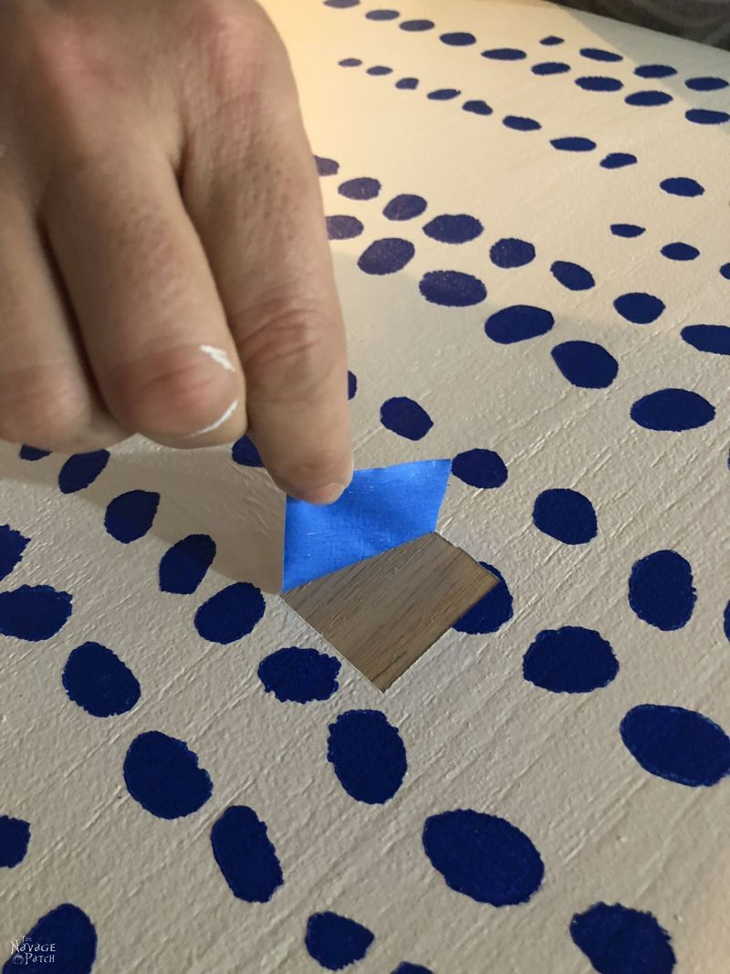 peeling masking tape from a painted surface