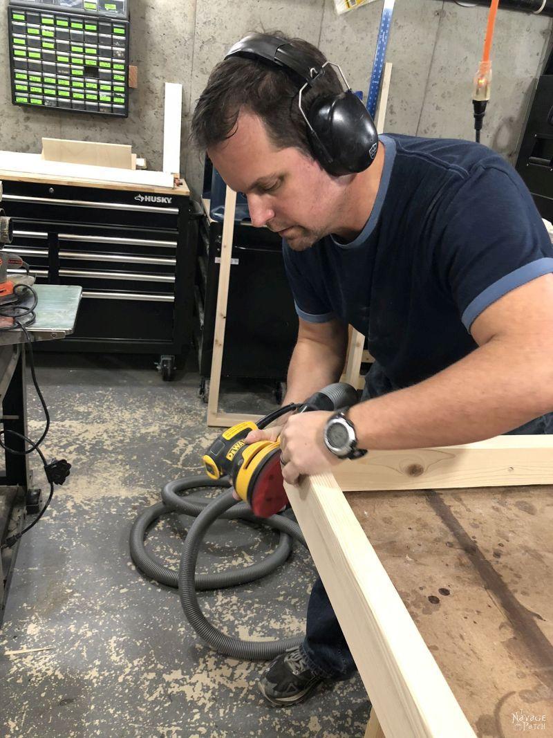 man sanding a guitar display frame