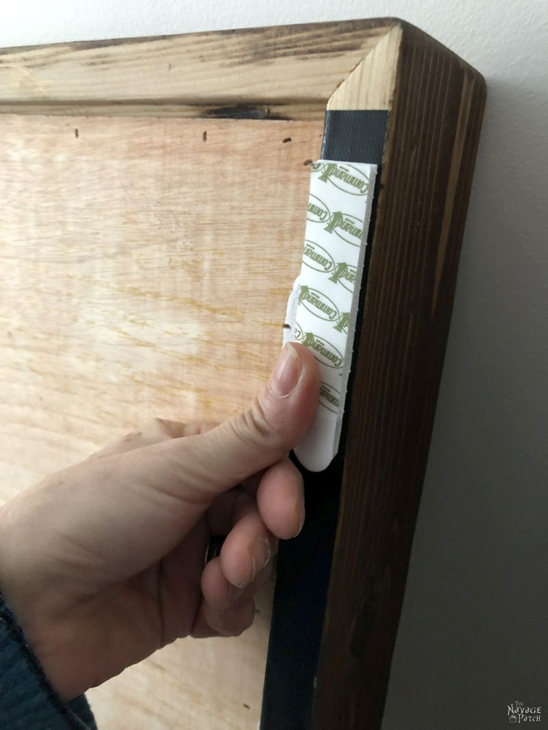 pressing a command strip to the back of a frame