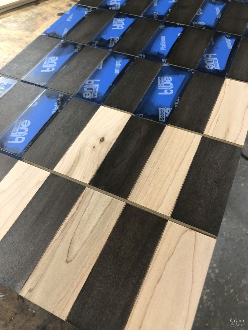 removing the masking tape from a diy vertical chess board after staining