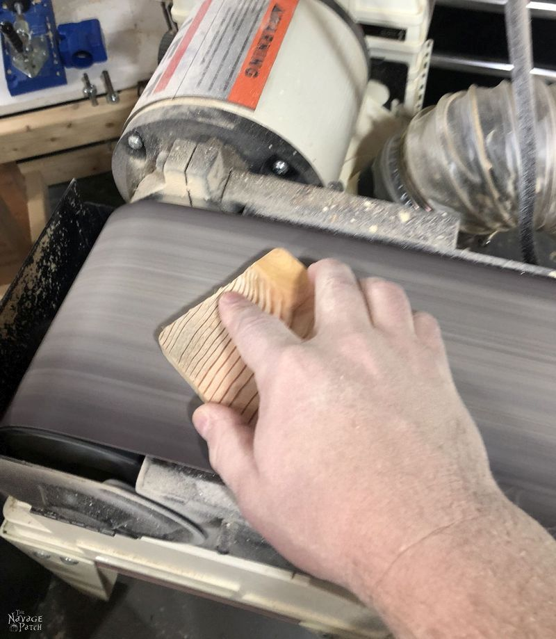 sanding a pine slice with a belt sander