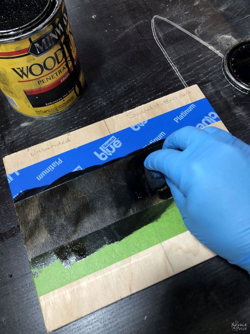hand applying stain to plywood