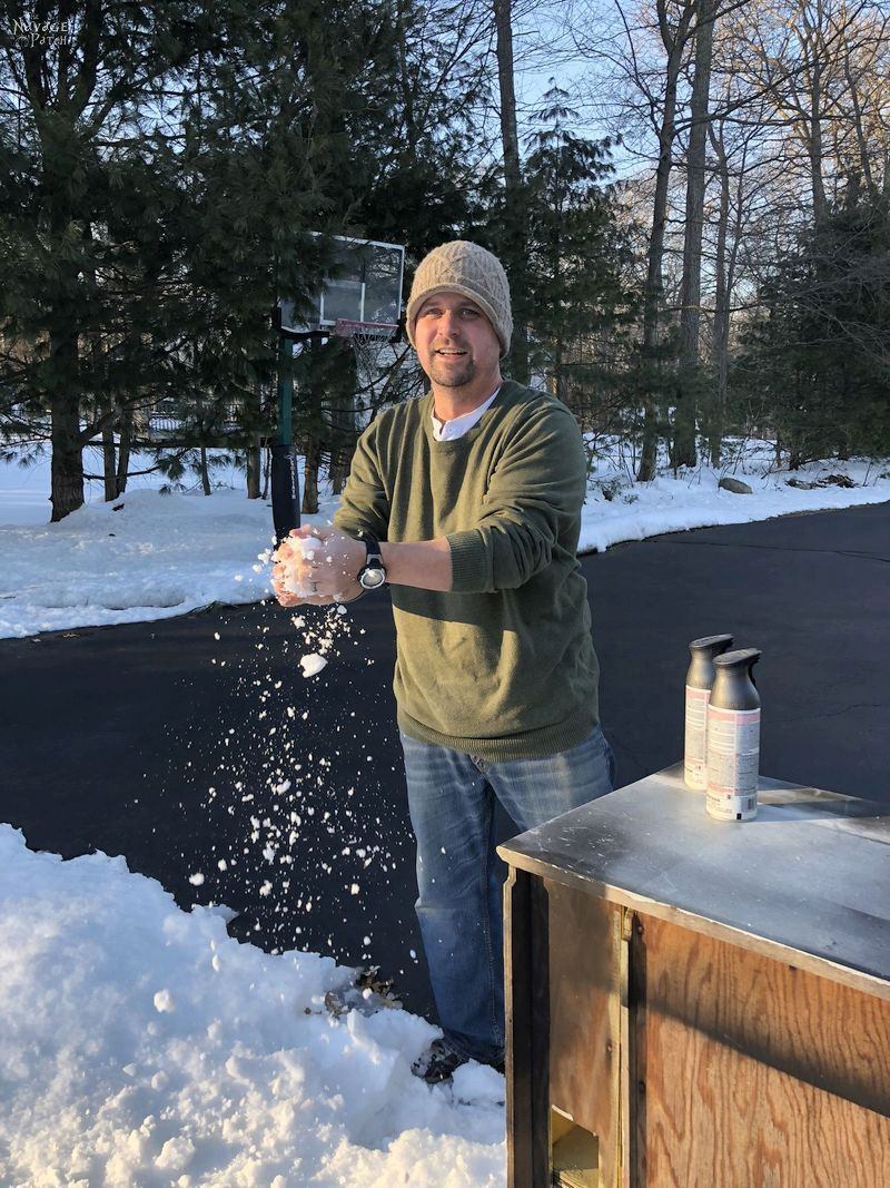 man washing his hands with snow