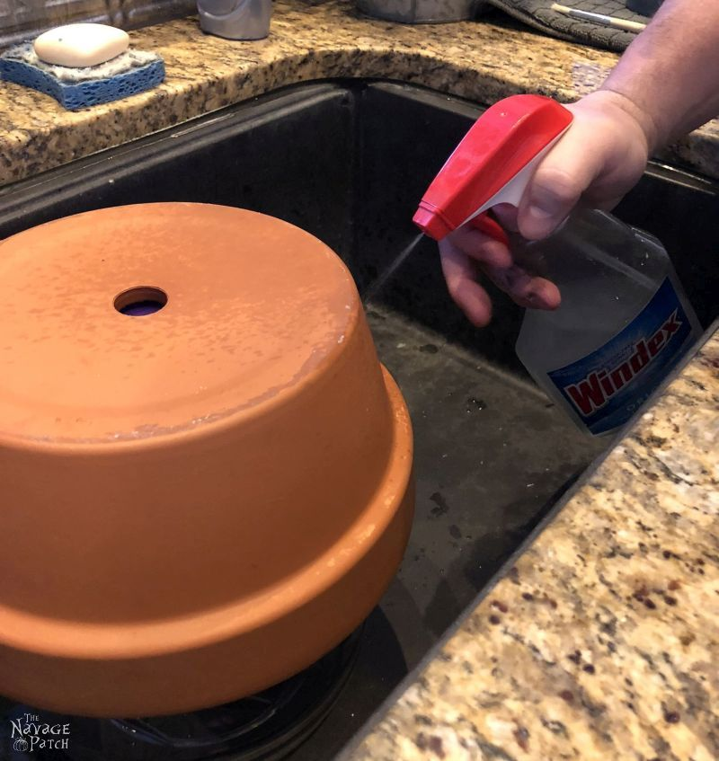 spraying a terra cotta pot with brine