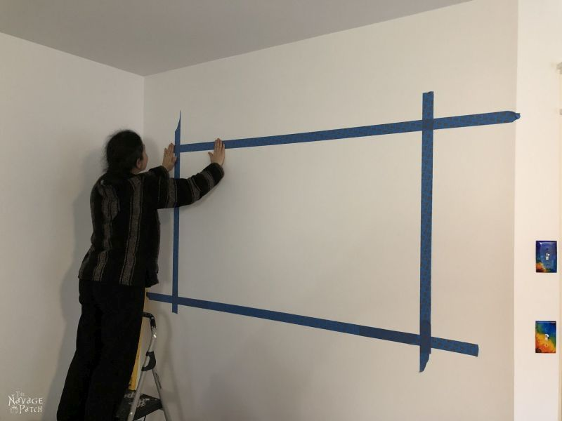 woman putting tape on a wall