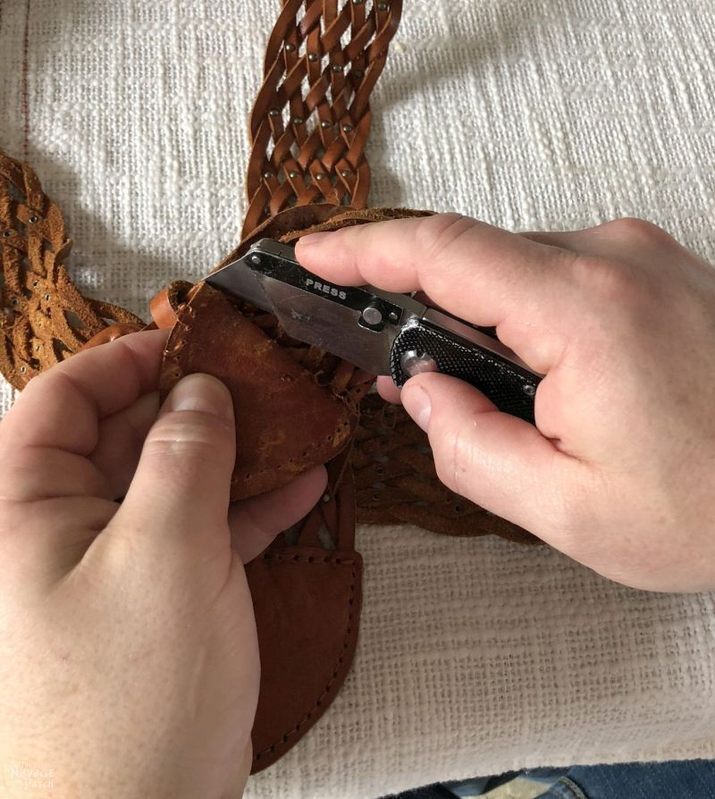 cutting the stitching on a leather belt