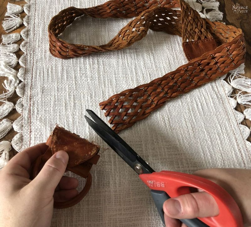 scissors cutting the buckle off a belt