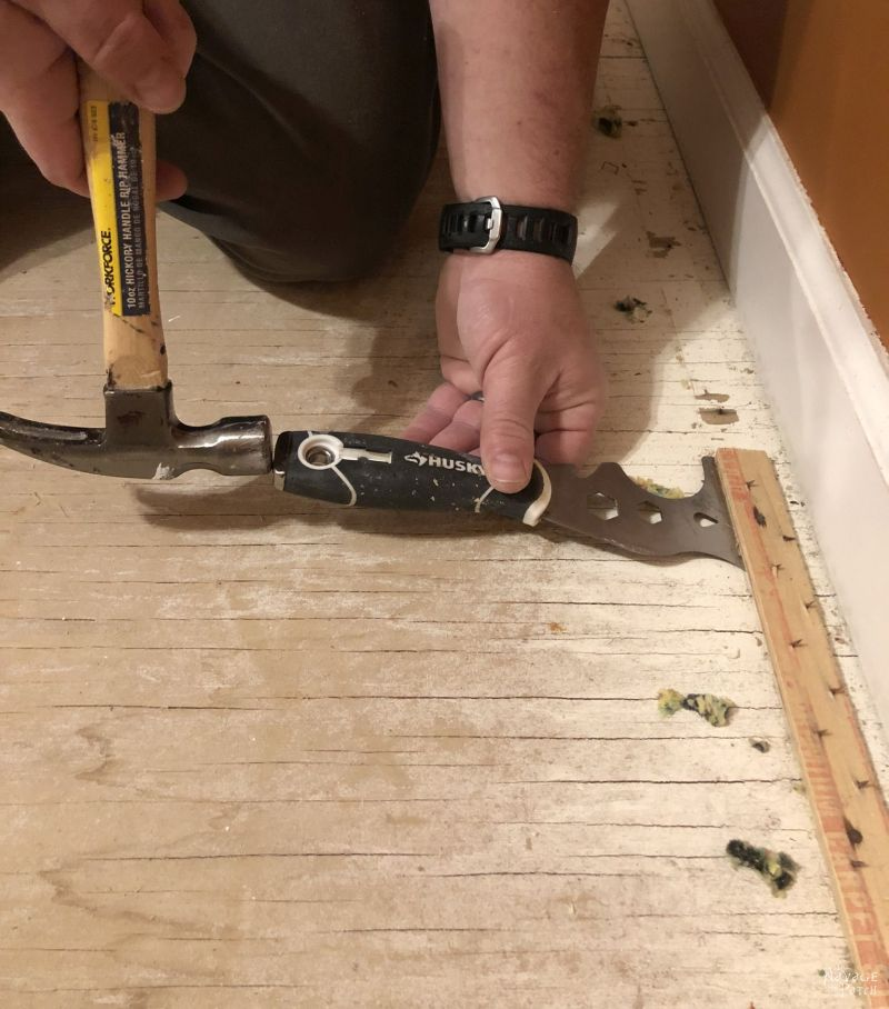 tapping a scraper under a carpet tack strip