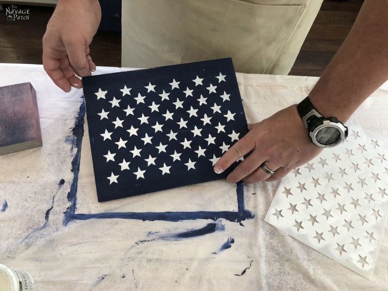 50 white stars stenciled on a blue painted piece of wood