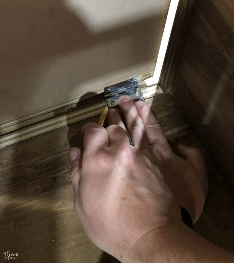 marking a hinge screw hole with a pencil