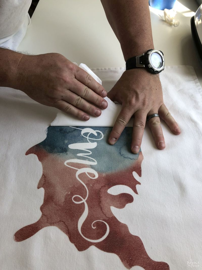 peeling the transfer paper from a patriotic pillow cover