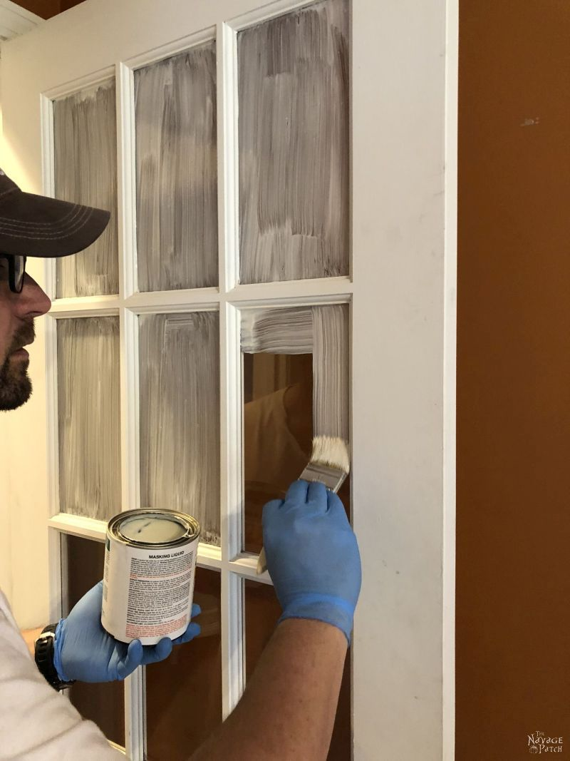 prepping to paint french doors by applying masking liquid to the panes