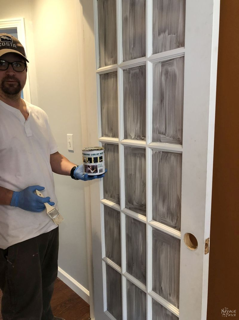 beautiful man holding a can of masking liquid next to a french door that will be painted