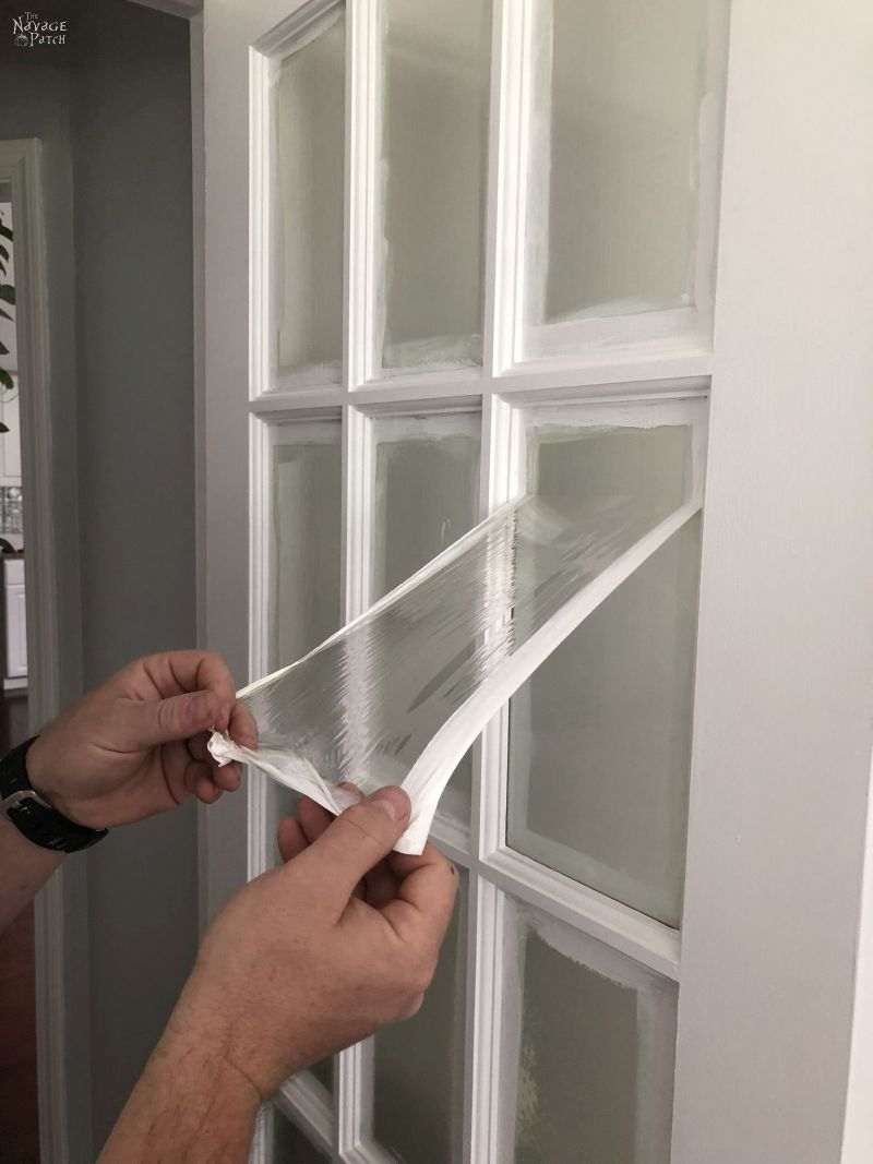 peeling the mask from a glass door panel