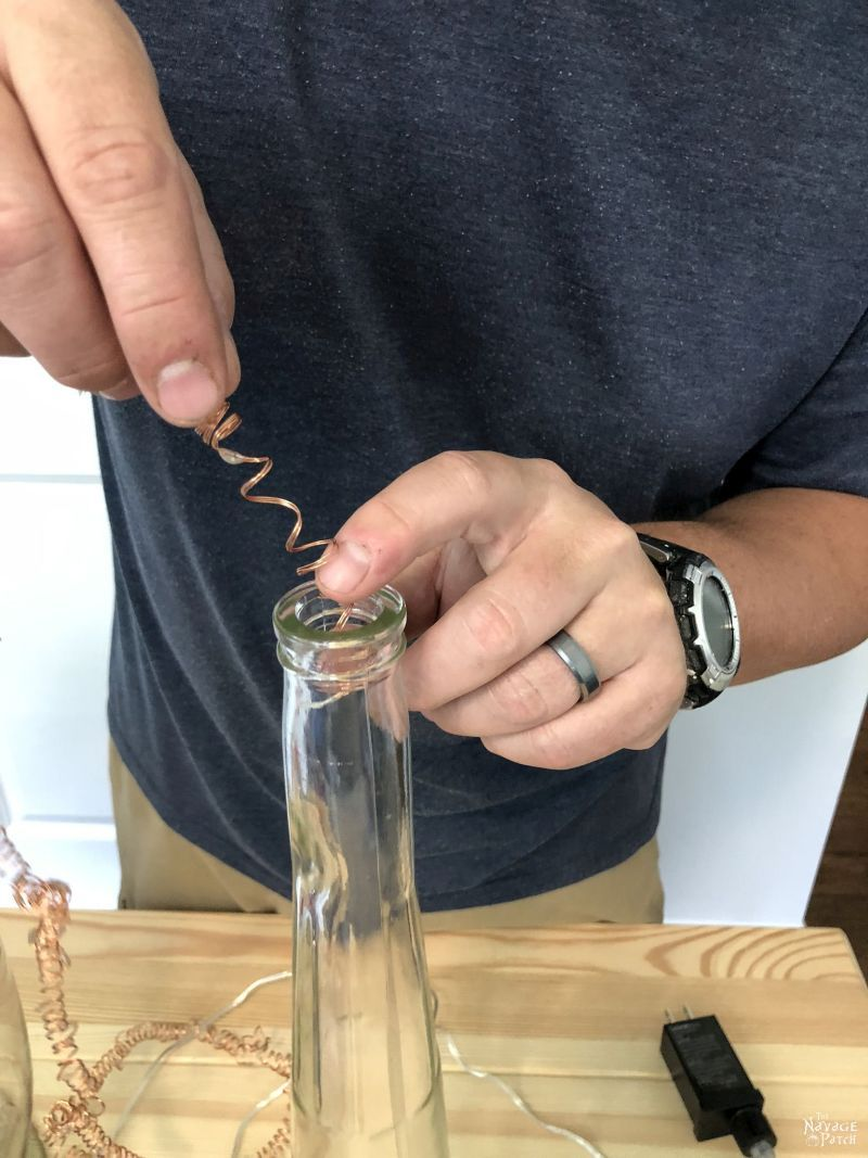 inserting fairy lights into a bottle