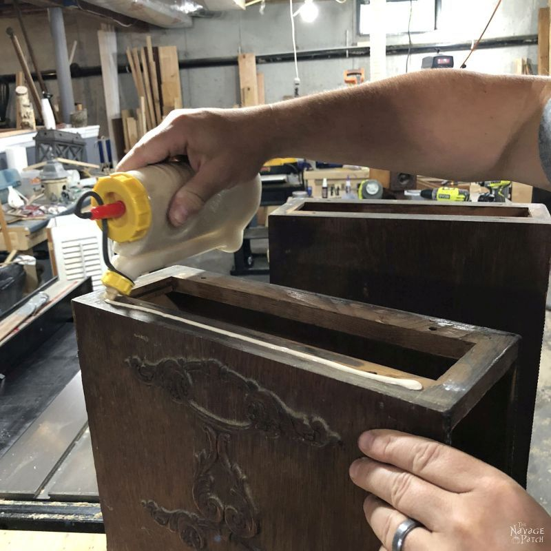 applying glue to the bottom of an antique sewing machine drawer cabinet