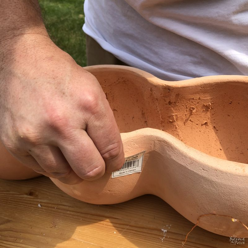 peeling a price tag from a terra cotta pot