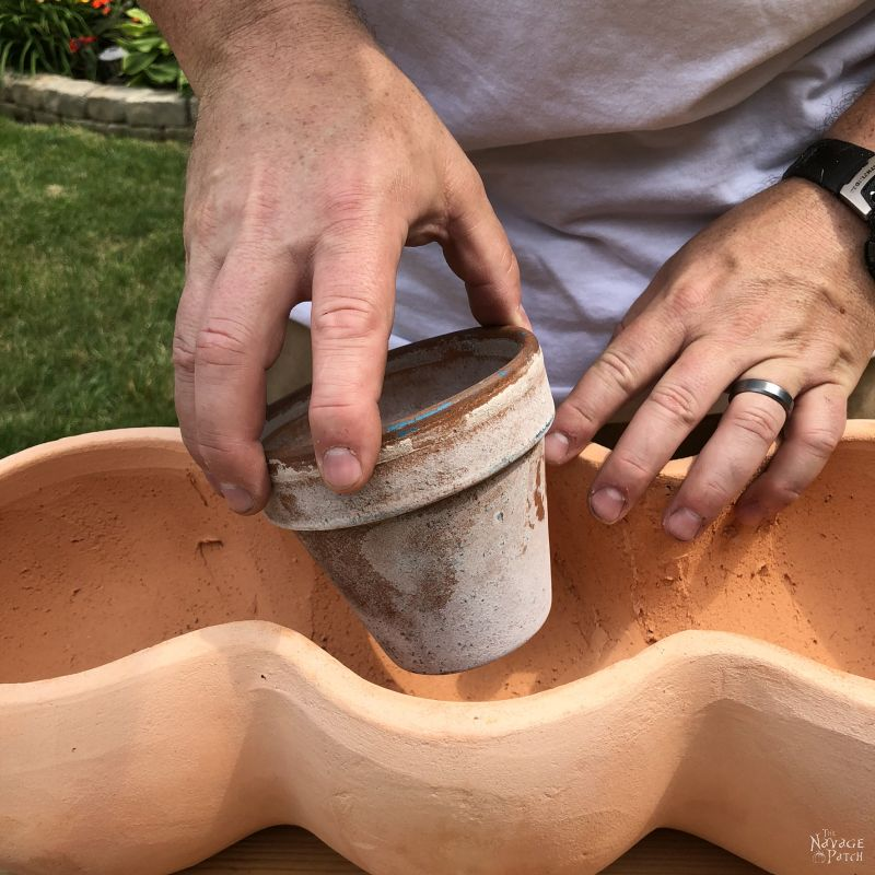 placing a small clay pot inside a larger one
