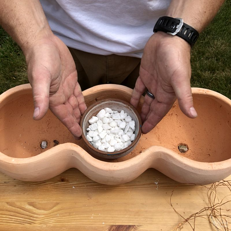 filling a clay pot with crushed stone