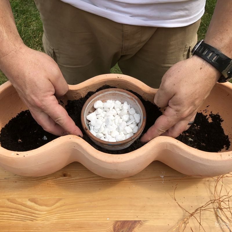 adding soil to a clay pot