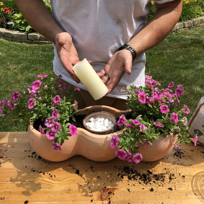 putting a candle into a clay pot planter