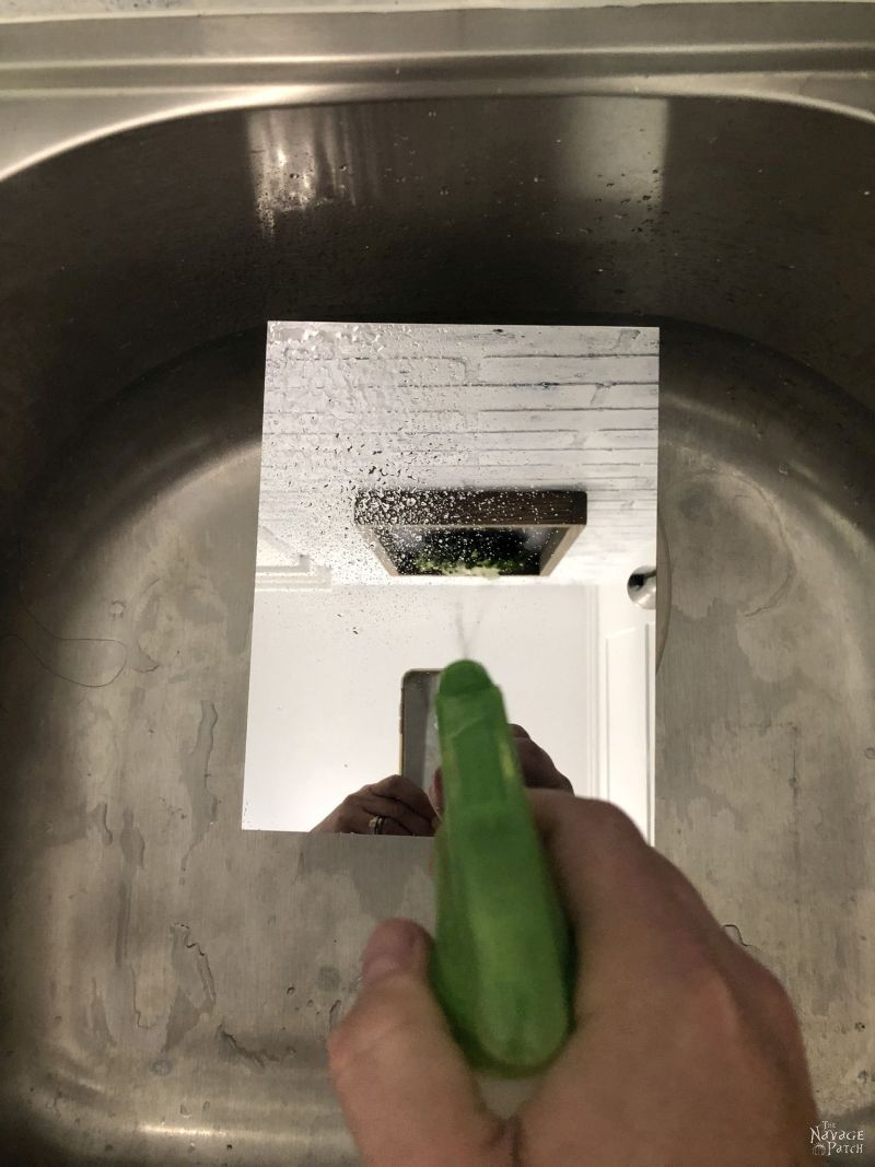 spraying bleach on a mirror